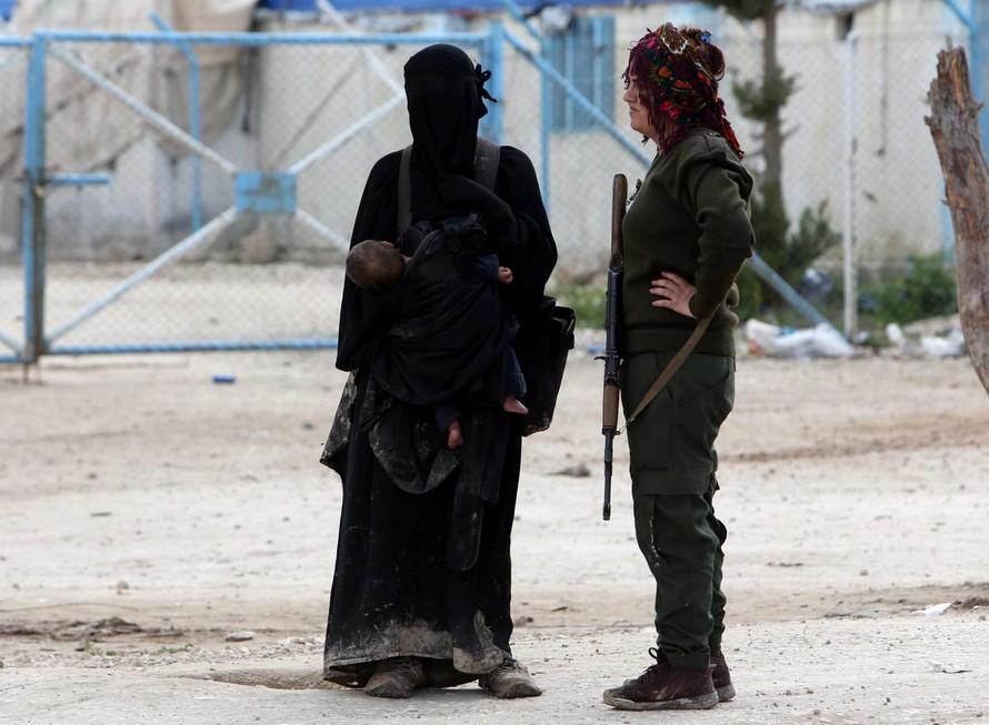Một thành viên SDF đứng cạnh vợ một tay súng IS ở trại al Hol ở Syria. Ảnh: Reuters