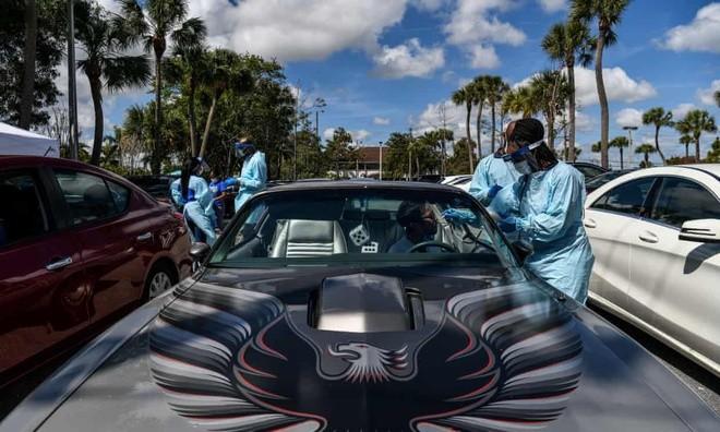 Nhân viên y tế lấy mẫuthử tại trạm xét nghiệm virus corona trên xe ở West Palm Beach, Florida. Ảnh: AFP.