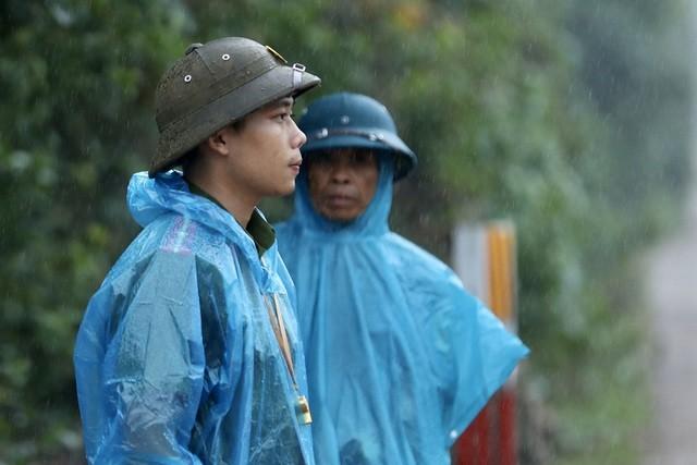 Trời đã bắt đầu mưa tại xã Phong Xuân, gây khó khăn và nguy hiểm cho công tác tìm kiếm. Các chiến sĩ công an vẫn túc trực đứng trong mưa làm nhiệm vụ.