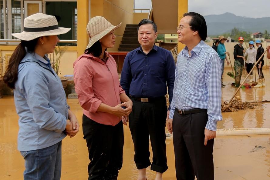 Giáo viên trường Tiểu học Hàm Ninh báo cáo Bộ trưởng Phùng Xuân Nhạ về tình hình lũ lụt và những thiệt hại mà nhà trường phải gánh chịu trong đợt lũ lịch sử vừa qua. Ảnh: Thế Đại