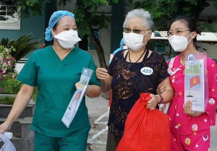 Điều dưỡng Đặng Thị Công (áo xanh) chia sẻ niềm vui với các bệnh nhân COVID-19 được công bố khỏi bệnh tại Đà Nẵng tháng 8/2020 (Ảnh: Lê Bảo)