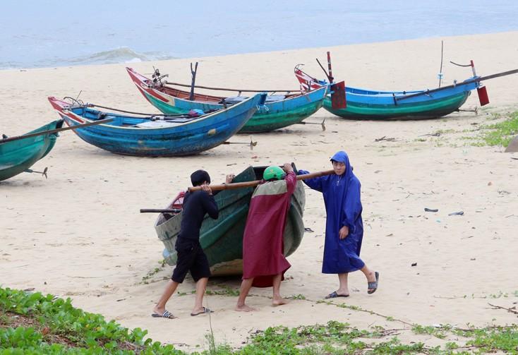 Ngư dân Quảng Bình vận chuyển thuyền lên bờ tránh bão. Ảnh: Báo Quảng Bình