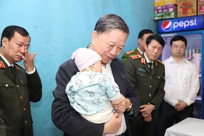 Bộ trưởng Công an Tô Lâm thăm gia đình chiến sỹ công an hy sinh tại Đồng Tâm. Ảnh: CAND