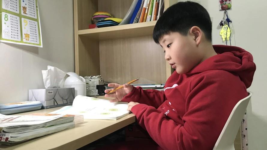 """Yoo Ju-chan, 8 tuổi, dành thời gian để học và chơi với chó vào kỳ nghỉ """"đặc biệt"""". Ảnh: The Washington Post"""