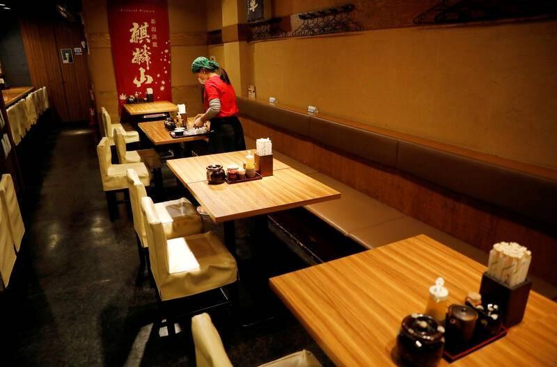 Một nữ nhân viên đang dọn bàn tại một nhà hàng ở Tokyo vào ngày 8/5. Ảnh: Reuters