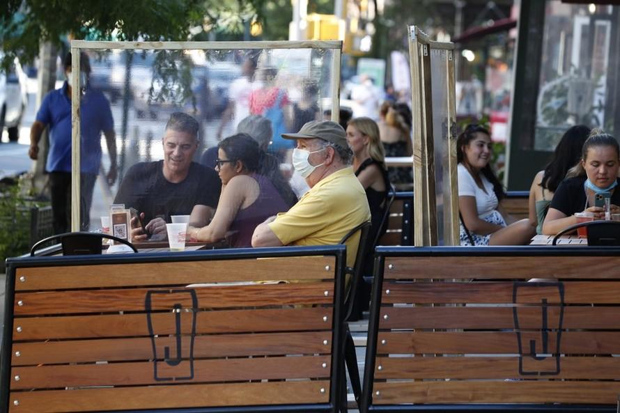 Thực khách ngồi ăn tại các bàn ngoài trời có vách nhựa ngăn cách. Ảnh: AP