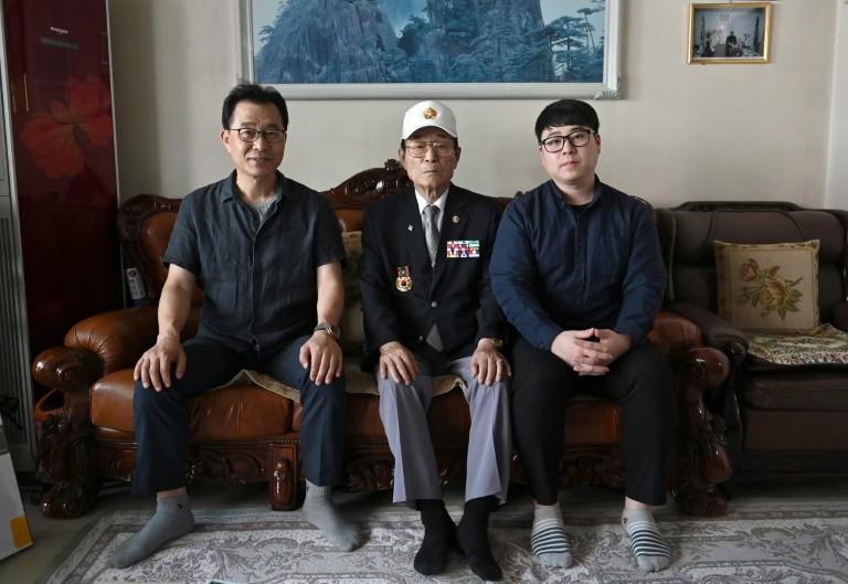Yang Tae-sung (giữa) cùng con trai Yang Kyung-mo (trái) và cháu trai Yang Hee-kon (phải) tại nhà riêng ở Seoul. Ảnh: AFP