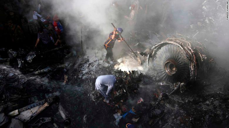 Các tình nguyện viên Pakistan đang đào bới tàn dư của chuyến bay PK 8303 vào ngày 22/5. Ảnh: CNN