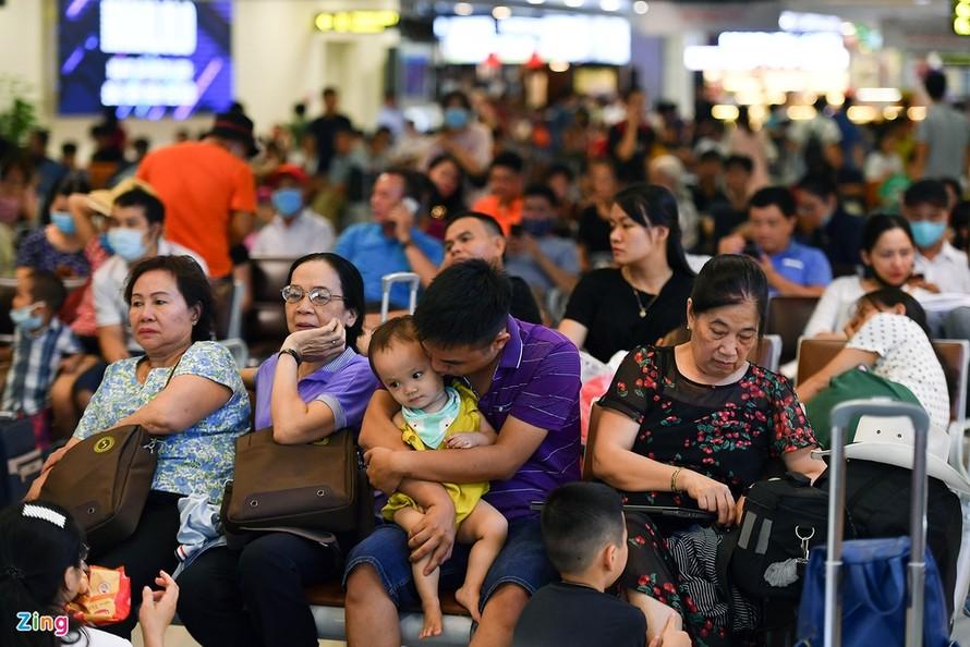 Phòng chờ nhà ga T1 Cảng hàng không Nội Bài chiều 20/7 đông nghẹt hành khách ngồi đợi đến giờ lên tàu bay.
