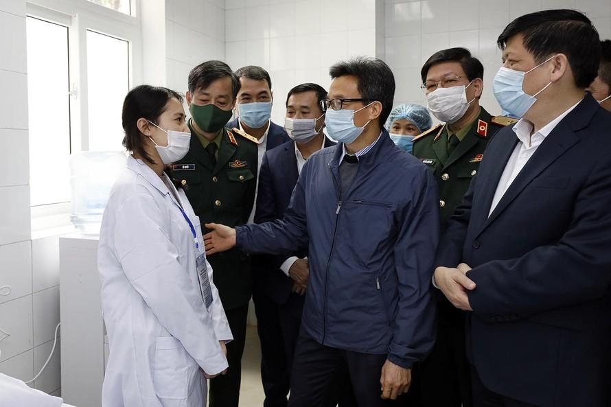 Phó Thủ tướng Vũ Đức Đam động viên một tình nguyện viên tiêm thử nghiệm vaccine phòng COVID-19.