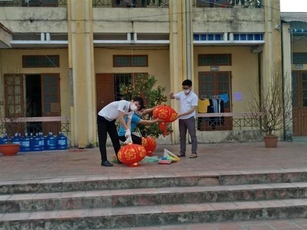 Phụ huynh tất bật trang trí sân trường khu cách ly tại trường tiểu học Lai Cách (huyện Cẩm Giàng) với mong muốn phần nào mang đến không gian Tết vào khu cách ly, đem lại niềm vui cho trẻ. Ảnh: TTXVN