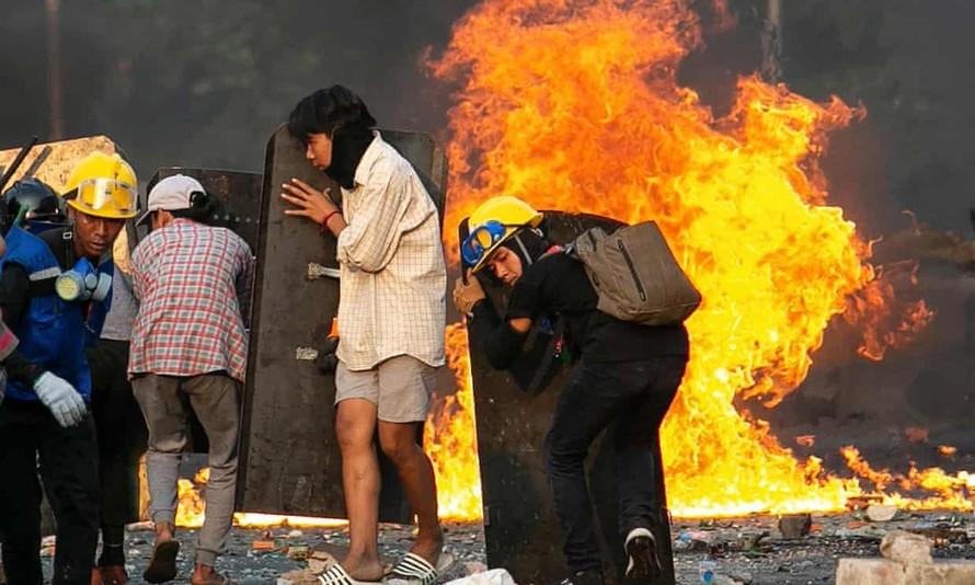 Người biểu tình tại Yangon núp sau các tấm khiên chắn. Ảnh: AFP