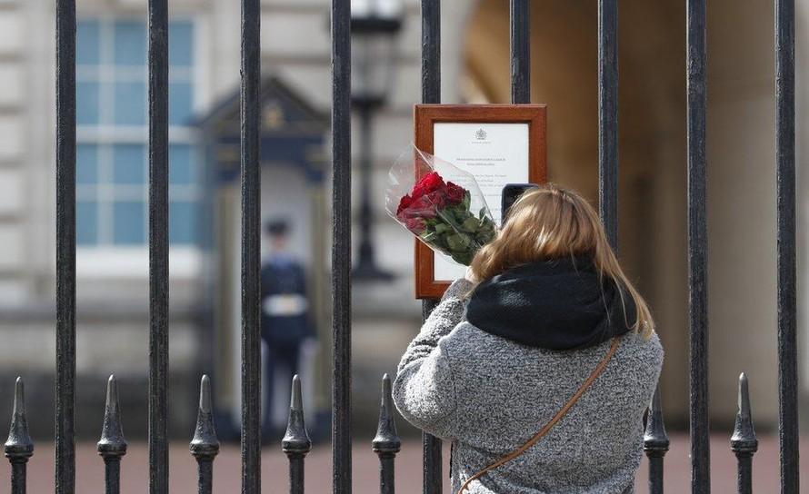 Một người phụ nữ đem theo hoa tới đặt trước cửa Cung điện Buckingham để tưởng nhớ Hoàng tế Philip. Ảnh: AP