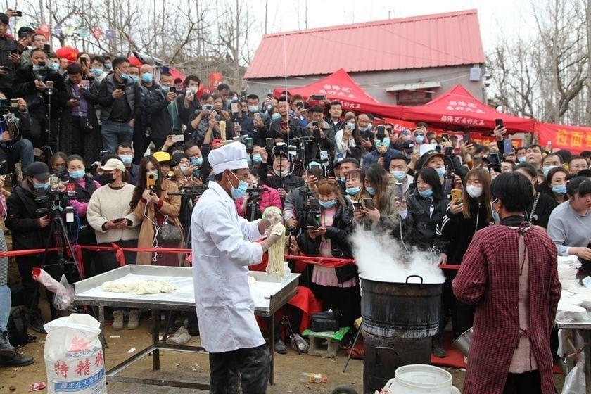 Đám đông tụ tập trước quán mỳ của ông Cheng để xem người này biểu diễn.