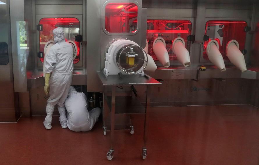 Các nhân viên vận hành máy chiết rót bên trong phòng thí nghiệm tại Viện Huyết thanh Ấn Độ. Ảnh: AP