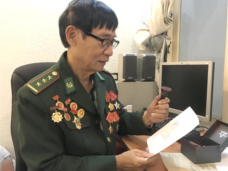 Ông Hoàng Minh Duyệt và kỷ vật vô giá là con dấu của Ngân hàng quốc gia Việt Nam dưới chế độ ngụy quyền Sài Gòn. Ảnh: bienphong.com.vn