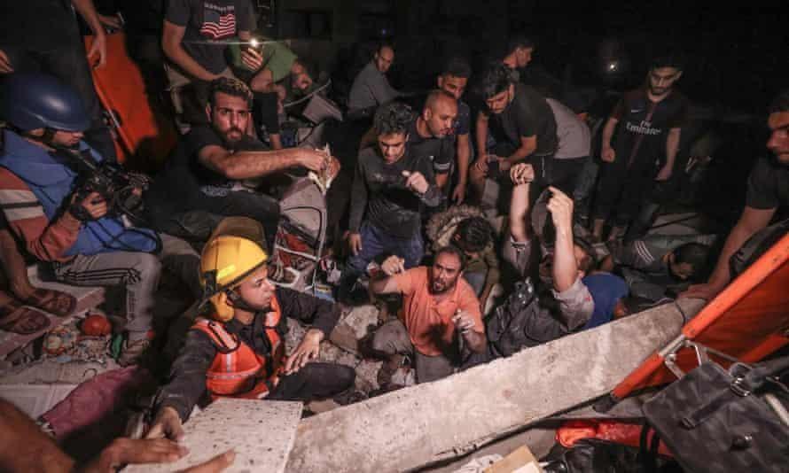 Lực lượng cứu hỏa Palestine khẩn trương tìm kiếm những người sống sót và các thi thể dưới đống đổ nát sau đợt pháo kích dữ dội vào thành phố Gaza hôm Chủ nhật. Ảnh: AFP