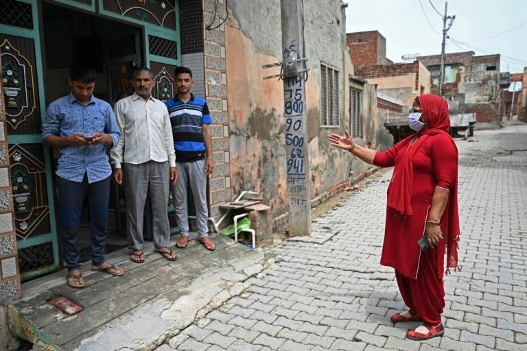 Một nhân viên y tế đi tuyên truyền cho người dân tại làng Kalwa (bang Haryana). Ảnh: AFP