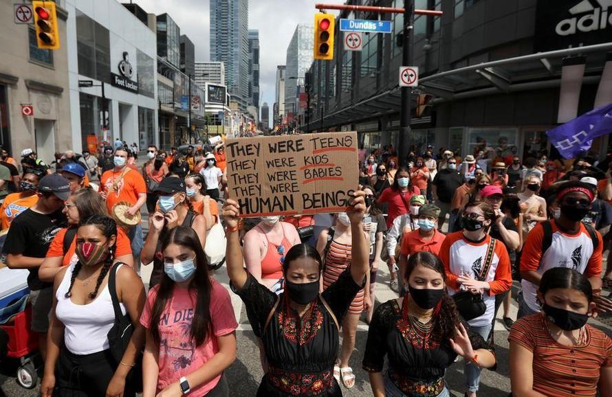 Người dân Toronto tuần hành để tưởng nhớ các nạn nhân qua đời trong các trường nội trú dành cho người bản địa hôm 1/7. Ảnh: Reuters