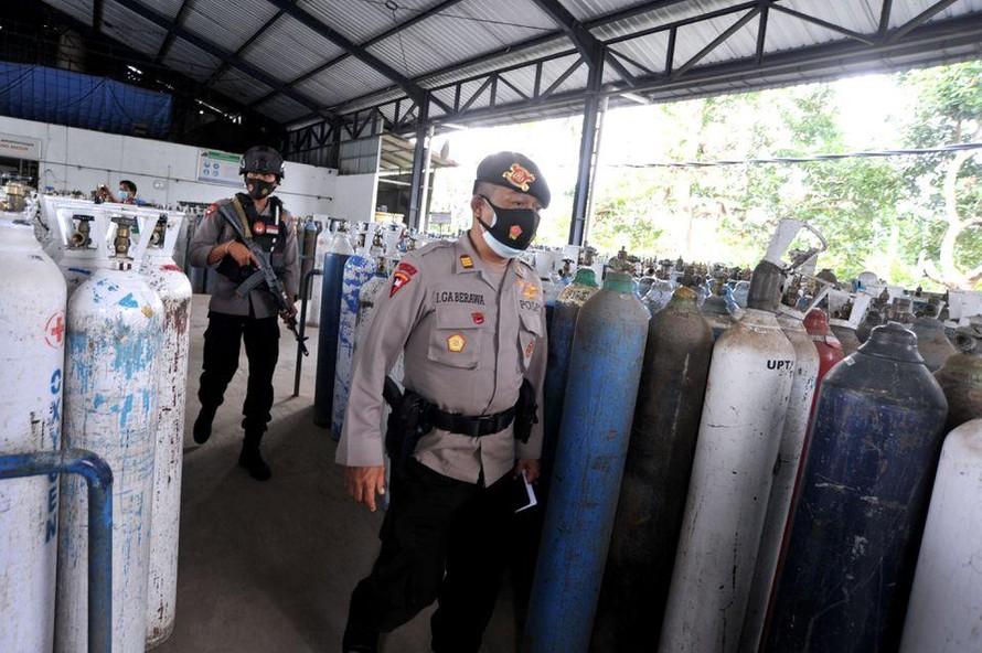 Cảnh sát trên đảo Bali tuần tra bảo vệ kho cất giữ oxy y tế. Ảnh: Reuters