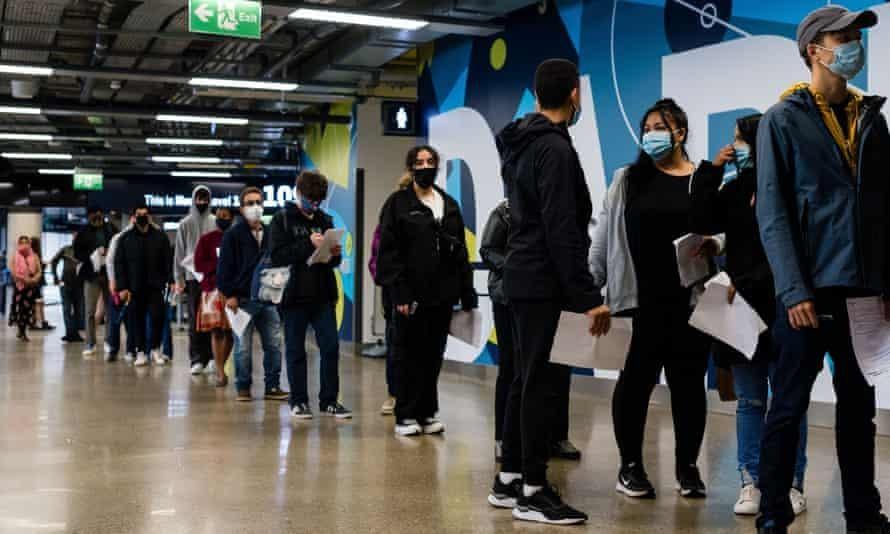 Người dân Anh xếp hàng làm thủ tục tiêm vaccine ngừa COVID-19 tại London. Ảnh: The Guardian