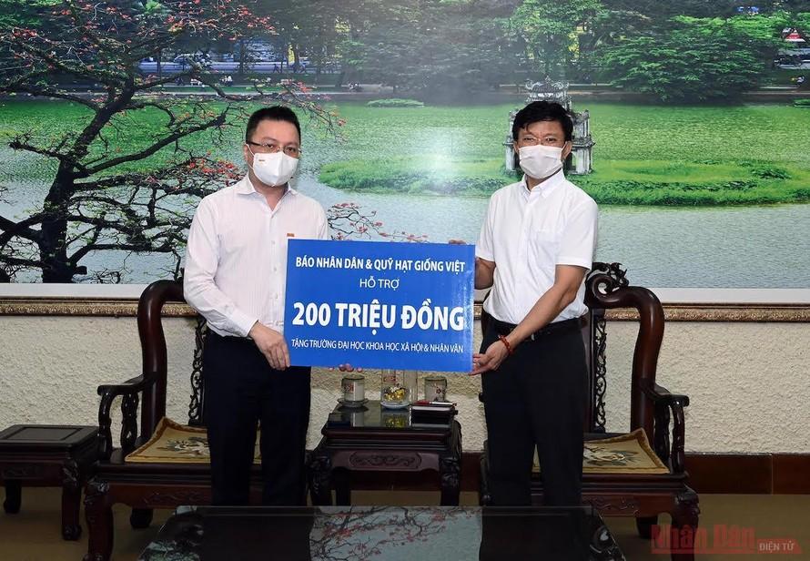 Đồng chí Lê Quốc Minh, Tổng Biên tập Báo Nhân Dân trao quà hỗ trợ Trường đại học Khoa học Xã hội và Nhân văn.