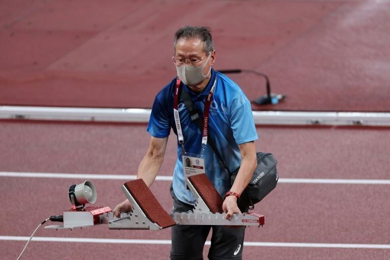 Một tình nguyện viên lớn tuổi chuẩn bị cho đường chạy điền kinh tại Olympic Tokyo 2020. Ảnh: AFP