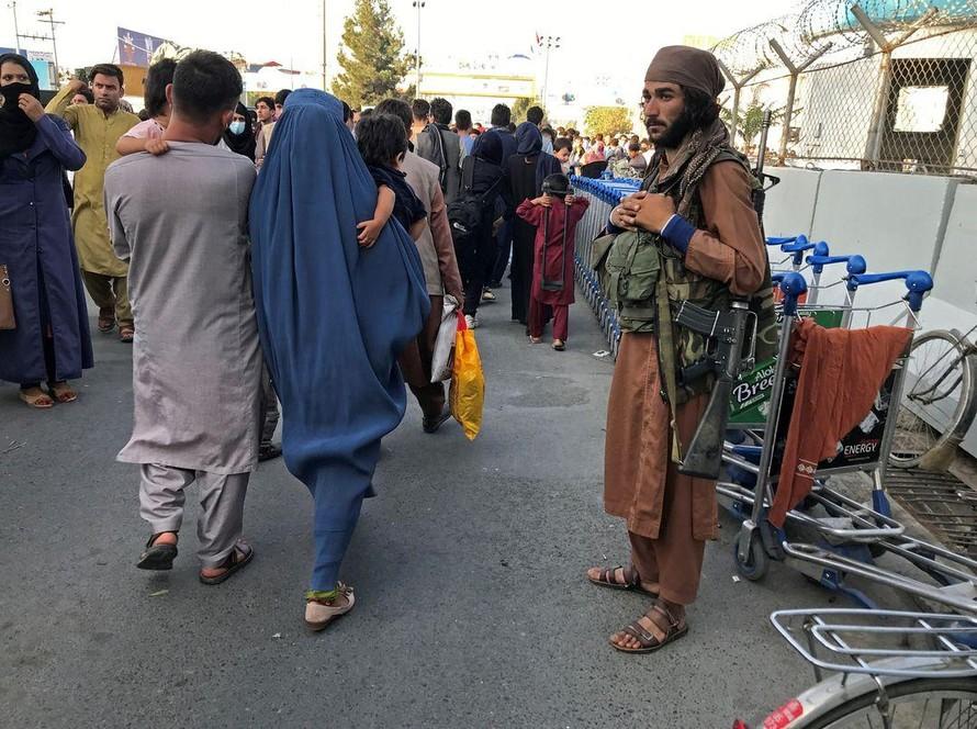 Một tay súng Taliban đứng nhìn người dân đi về phía cổng vào của sân bay quốc tế Hamid Karzai ở Kabul, Afghanistan. Ảnh: Reuters