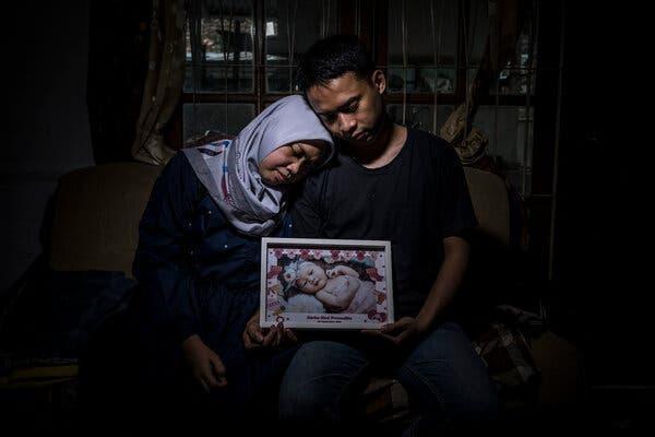 Vợ chồng Debiyantoro cùng di ảnh cô con gái Kimi 22 tháng tuổi qua đời vì COVID-19. Ảnh: NY Times