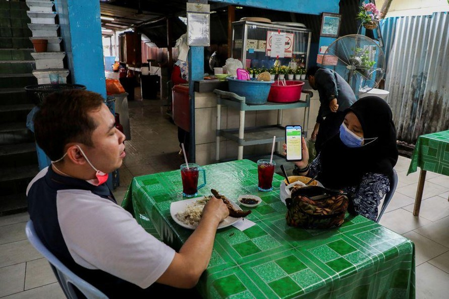 Thực khách tại thủ đô Kuala Lumpur của Malaysia xuất trình chứng nhận tiêm chủng để được dùng bữa trong nhà hàng. Ảnh: Reuters