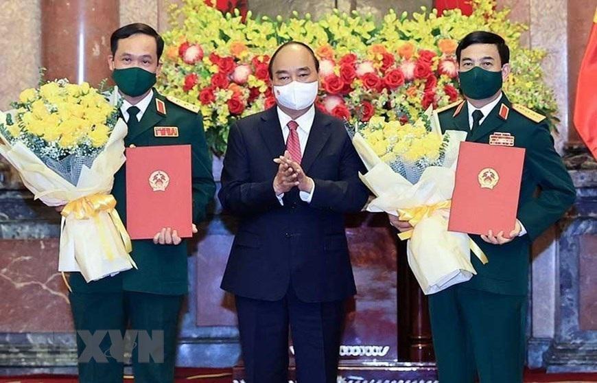 Chủ tịch nước Nguyễn Xuân Phúc trao quyết định thăng quân hàm, hoa chúc mừng Bộ trưởng Quốc phòng Phan Văn Giang (phải) và Thứ trưởng Vũ Hải Sản. Ảnh: TTXVN