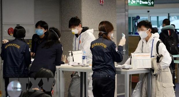 Nhân viên tiến hành công tác kiểm dịch đối với hành khách tại sân bay Incheon, phía tây thủ đô Seoul, Hàn Quốc, ngày 23/3/2020. (Nguồn: Yonhap/TTXVN)