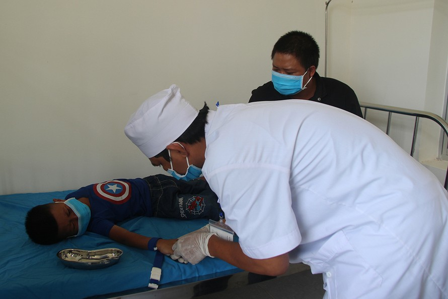 Bác sĩ lấy mẫu xét nghiệm bạch hầu tại Trung tâm Y tế huyện Krông Nô. Ảnh: Ngọc Oanh.