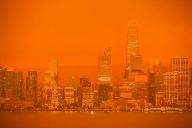 Các tòa cao ốc của San Francisco mờ ảo giữa làn khói mờ màu cam nhìn từ đảo Treasure.