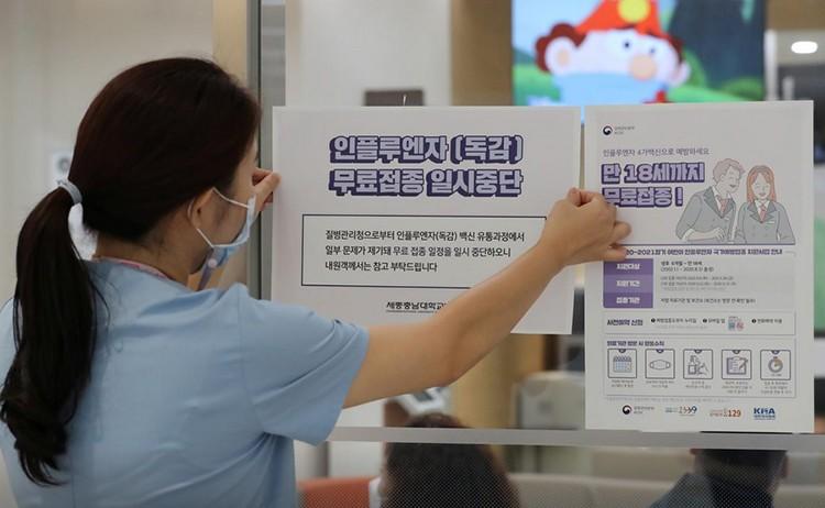 Nhân viên y tế dán thông báo tạm ngưng chương trình tiêm phòng cúm tại một bệnh viện ở Sejong. Ảnh: Yonhap