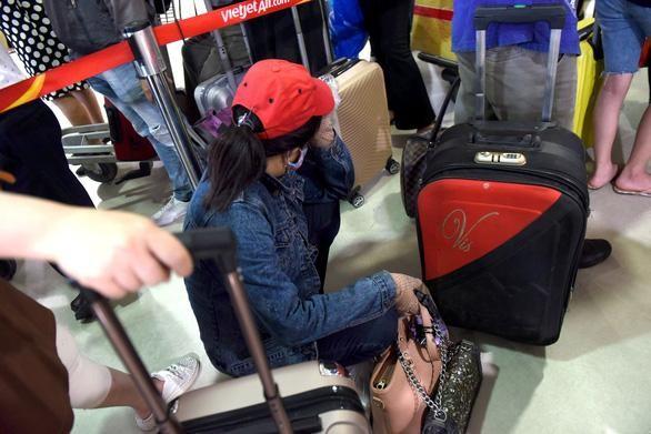 Mệt mỏi chờ đợi trước cửa khu vực an ninh soi chiếu tại nhà ga quốc nội sân bay Tân Sơn Nhất trưa 18/4 - Ảnh: Duyên Phan