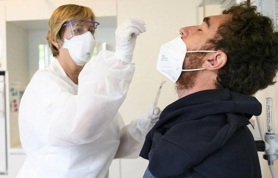 Nhân viên y tế lấy mẫu xét nghiệm COVID-19 tại Thụy Sĩ. (Ảnh: Swiss Info/TTXVN)