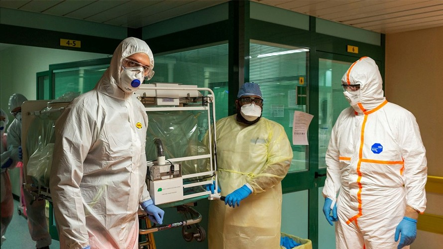 Nhân viên y tế đeo khẩu trang và mặc đồ bảo hộ khi tiếp xúc với bệnh nhân nhiễm virus corona. - Ảnh: Reuters.