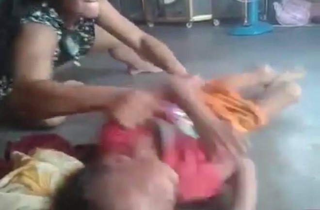 Người phụ nữ nằm xuống rồi ngồi dâỵ hất bé trai và tát vào mặt.