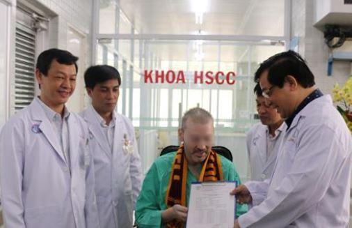 Đại diện Bộ Y tế và Bệnh viện Chợ Rẫy trao giấy xuất viện và chứng nhận âm tính với virus SARS-CoV-2 cho bệnh nhân 91 - Ảnh: TTXVN