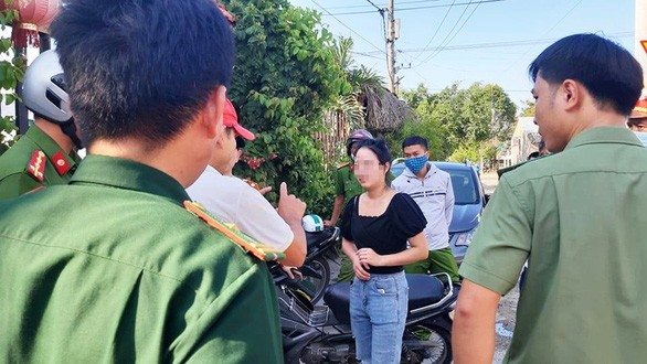 Lực lượng chức năng làm việc với một phụ nữ trong nhóm người Trung Quốc bỏ chạy khỏi khu lưu trú tại tỉnh Quảng Nam chiều 18/7 - Ảnh: Tuổi Trẻ