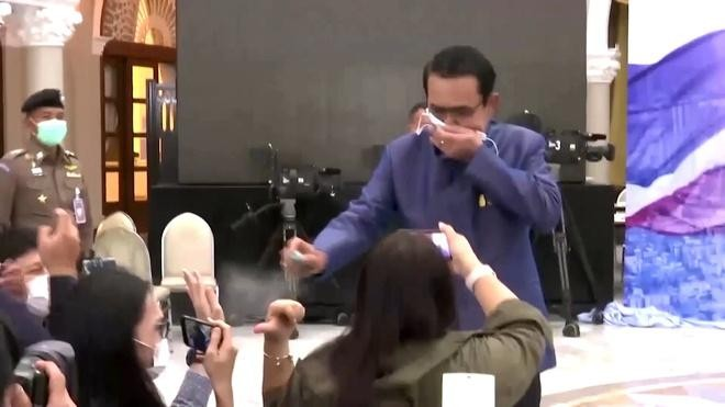 Khoảnh khắc Thủ tướng Prayuth xịt dung dịch sát khuẩn vào phóng viên khi bị hỏi về vấn đề của chính phủ. - Ảnh: BKP.