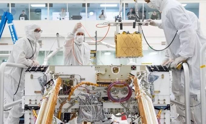 Các nhà nghiên cứu lắp MOXIE dưới bộ khung gầm của robot Perseverance. - Ảnh: NASA.