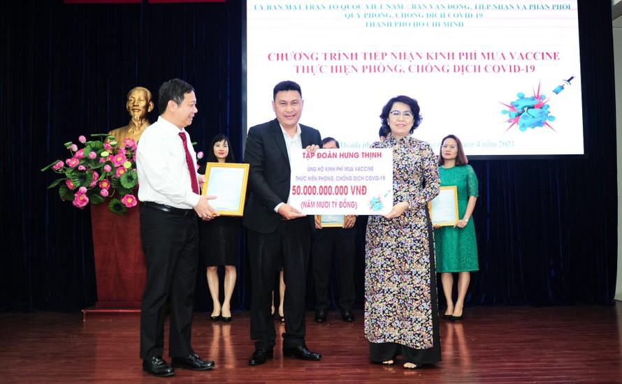 Ông Nguyễn Nam Hiền - Phó Tổng Giám đốc Tập đoàn Hưng Thịnh trao bảng tượng trưng ủng hộ 50 tỷ đồng kinh phí mua vắc-xin phòng ngừa Covid-19 cho bà Tô Thị Bích Châu, Chủ tịch Ủy ban Mặt trận Tổ quốc Việt Nam TP.HCM.
