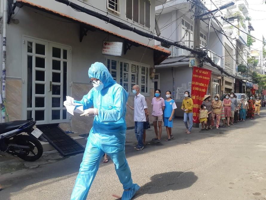 Nhân viên y tế làm thủ tục xét nghiệm cho người dân tại phường 15 (quận Bình Thạnh). Ảnh: Bá Trình