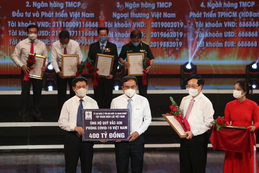 Chủ tịch HĐTV EVN Dương Quang Thành (giữa) trao biểu trưng số tiền 400 tỷ đồng ủng hộ Quỹ vắc-xin phòng chống COVID-19. Ảnh: EVN.