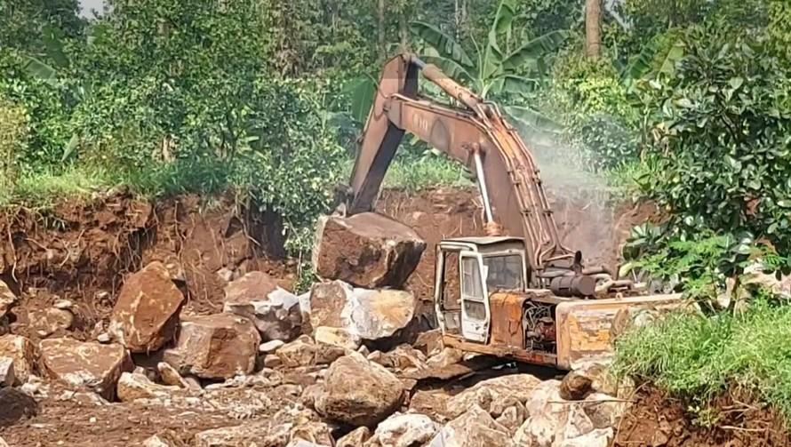 Xe đào đang khai thác đá mồ côi trong rừng phòng hộ.