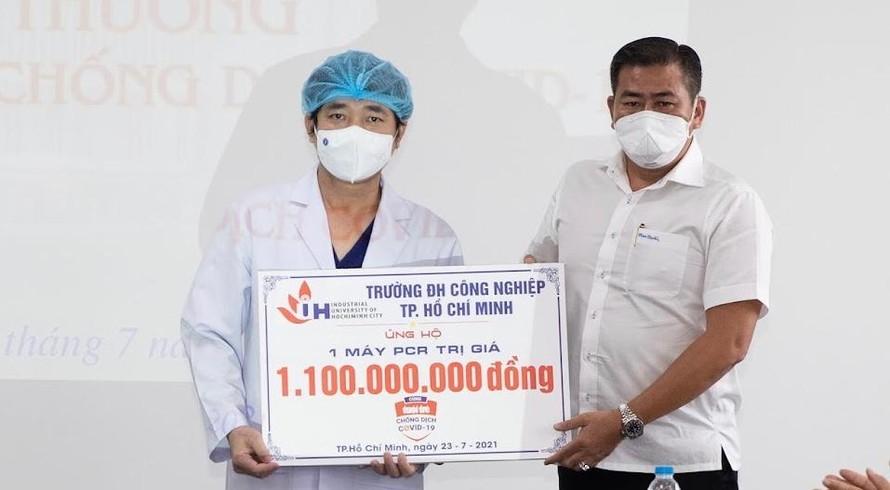 TS. Phan Hồng Hải – Hiệu trưởng Trường Đại học Công nghiệp TP.HCM (phải) trao bảng tượng trưng ủng hộ máy xét nghiệm RT-PCT cho bệnh viện An Bình.