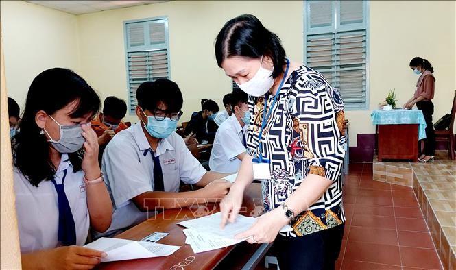 Giám thị hướng dẫn cho thí sinh làm thủ tục dự thi trong Kỳ thi tốt nghiệp Trung học phổ thông.