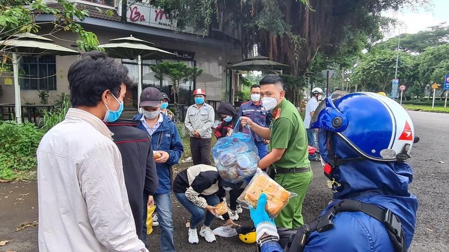 Lực lượng Công an hỗ trợ phân phối thức ăn và nước uống cho người dân trên hành trình về quê nhà.
